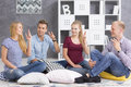 People sitting on pillows and learning sign language