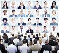 People sitting with set of business people s faces Royalty Free Stock Photo