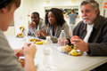 People sitting at table eating food in homeless shelter talking to each other Stock Photos