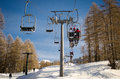 People and skiers on chairlift aerial lift and skilift in sunny day Stock Images