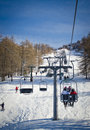 People and skiers on chairlift aerial lift and skilift in sunny day Stock Image
