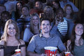 People with soda and popcorn watching movie in theatre group of happy multiethnic Stock Photo