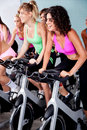 People spinning on bicycles in a gym Stock Photography