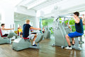 People in sport gym on machines group of men train machine a fitness club or Stock Image