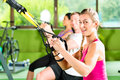 People in sport gym on suspension trainer Stock Photo
