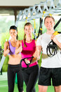 People in sport gym on suspension trainer group of exercising with fitness club or Stock Images