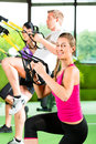 People in sport gym on suspension trainer group of exercising with fitness club or Stock Photography