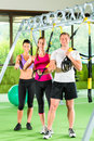 People in sport gym on suspension trainer gruppe von menschen trainieren mit schlingentrainer oder fitnessstudio Stock Photos
