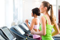 People in sport gym on treadmill running or fitness club two women exercising to gain more fitness Royalty Free Stock Photos