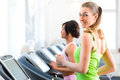 People in sport gym on treadmill running or fitness club two women exercising to gain more fitness Stock Photo