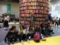 People taking souvenir photo in front of the iconic book tower at international book fair Royalty Free Stock Photo