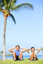 People training sit ups outside fitness couple doing situps exercise during outdoor cross workout happy young multiracial Royalty Free Stock Photos