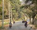 People and vehicles on rural road in Mandalay, Myanmar