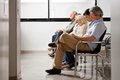 People waiting for doctor in hospital lobby row of multiethnic sitting side by side while Royalty Free Stock Photos