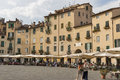 People walk and have a rest in cafes along amphitheatre square unrecognizable lucca italy the situated on Stock Photo