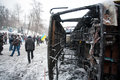 People walking around burned street with broken mi kiev ukraine military bus on the barricades of snowy city during anti Stock Image