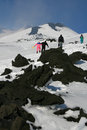 People walking on etna volcano covered by snow sicily Stock Photos