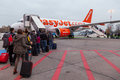 People walking in a runway to enter an easyjet plane berlin germany november the company operates routes across europe and between Royalty Free Stock Images