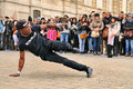 People watch a homeless streetdancer doing breakdance and dance moves in the streets of paris to earn some money mar on Stock Photos