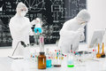 People working in a chemistry lab close up of two scientists testing laboratory substances on table with colorful liquids and Royalty Free Stock Photos