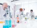 People working in chemistry lab general view of analyzing under microscope on a table with colorful liquids and tools Stock Image