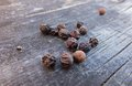 Pepper in corns peppercorns dissipated on the old gray wooden table Stock Image
