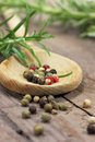 Pepper and rosemary on wooden table Stock Photos