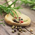 Pepper and rosemary on wooden table Royalty Free Stock Image