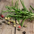 Pepper and rosemary on wooden table Royalty Free Stock Photo