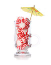 Peppermint candy in glass and cocktail umbrella isolated on white. Concept. Red striped mint Christmas candy Royalty Free Stock Photo