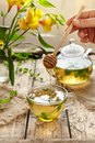 Peppermint tea with honey in glass cup, teapot and flowers Royalty Free Stock Photo