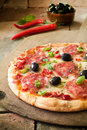 Pepperoni pizza with spicy salami and olives on a bed of tomato paste and melted cheese sprinkled fresh basil Royalty Free Stock Photos
