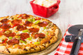 Pepperoni and Vegetable Pizza with Cheese and Cutter Royalty Free Stock Photo