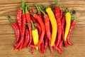Peppers colorful fresh cayenne on a wooden background Royalty Free Stock Photography