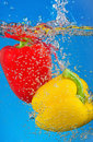 Peppers are dropped into water Stock Photography