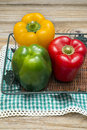 Peppers miscellaneous colored in a basket on a wooden table Stock Photography