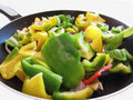 Peppers and onions in the cooking pan on white background Royalty Free Stock Photo