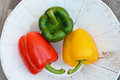 Peppers in three colors on a white natural plate Royalty Free Stock Photo
