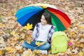 Perfect autumn day of cheerful kid under colorful umbrella with school bag sitting in fall season park enjoying good Royalty Free Stock Photo