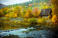 Perfect autumn scenery with old abandoned house and calm river surrounded by colourful trees Stock Photography