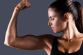 Perfect bicep beautiful young sporty woman examining her while standing against grey background Stock Photos