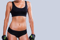 Perfect body close up of young sporty woman with standing against grey background Stock Photography