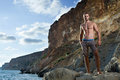 Perfect body man with naked torso on mountains and sea background brown trousers Royalty Free Stock Photos
