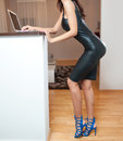 Perfect body woman in short tight fit leather dress working on the laptop in living room. Side view of sensual young female Royalty Free Stock Photo