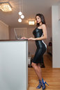 Perfect body woman in short tight fit leather dress working on the laptop in living room side view of sensual young female with Stock Photo