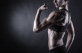 Perfect female body attractive athletic woman showing biceps on a dark background Royalty Free Stock Photography