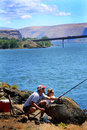 Perfect fishing spot a couple sturgeon with reel and pole in the columbia river with maryhill bridge in the background Stock Photography