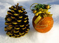 Perfect gold christmas ball with ribbon and cone on snow Royalty Free Stock Photo