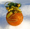 Perfect gold christmas ball with ribbon on snow Royalty Free Stock Photo