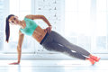 Perfect side plank full length of young beautiful woman in sportswear doing and looking at camera in front of window at gym Stock Photos